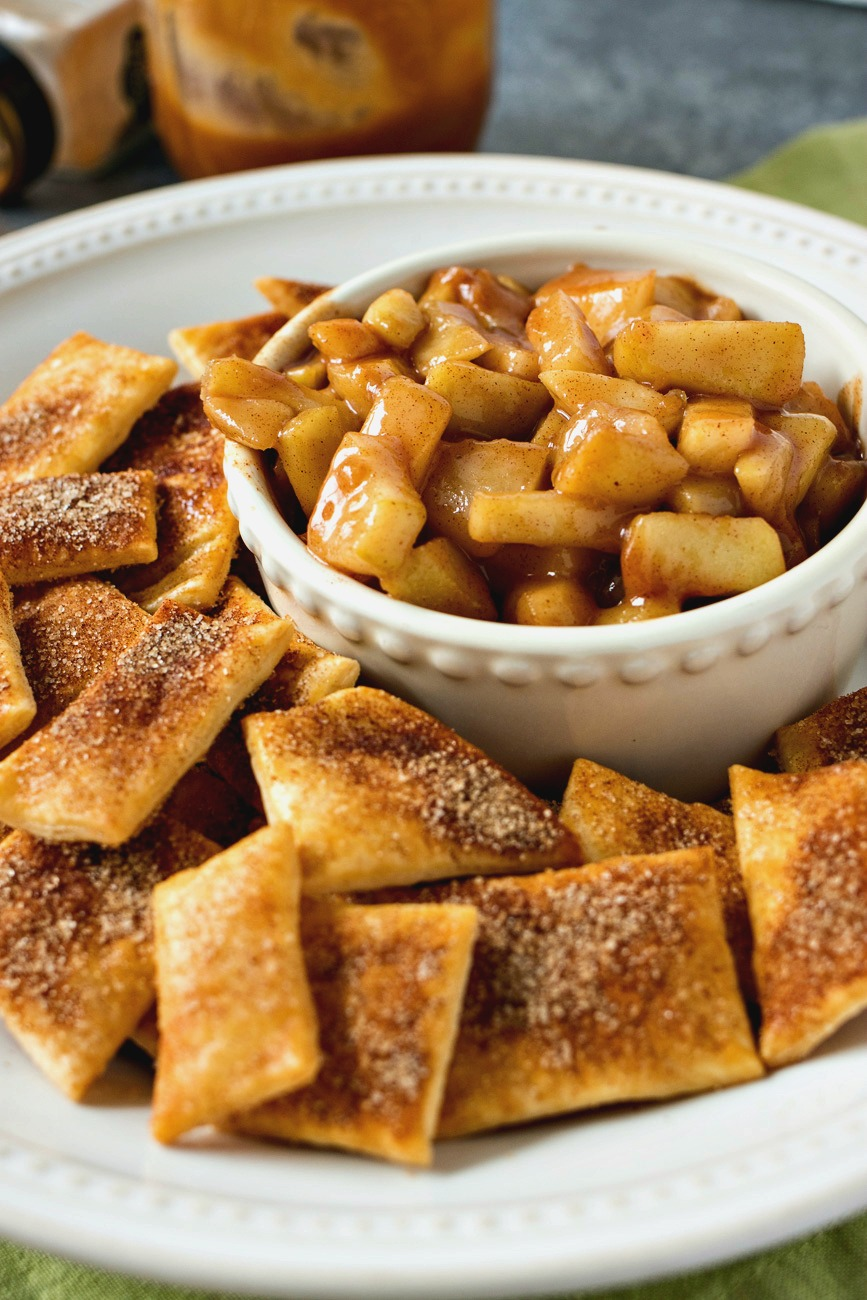 Salted Caramel Apple Pie Dip in a bowl with plate of Pie Crust Chips