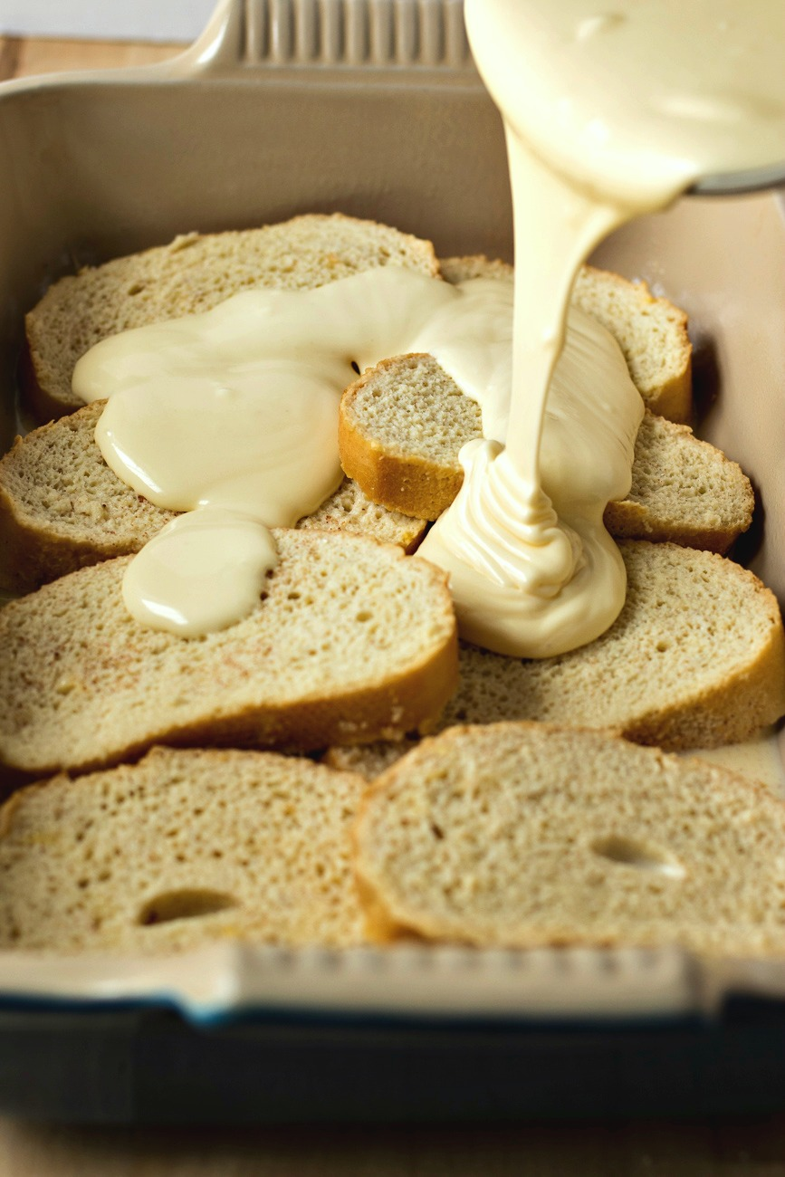 Pouring cream cheese filling over slices of bread in the casserole dish
