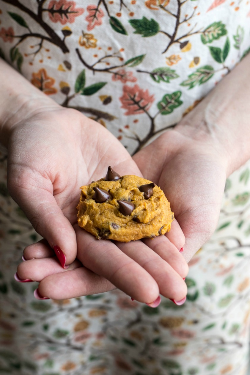 Two hands holding a Pumpkin Chocolate Chip Cookie