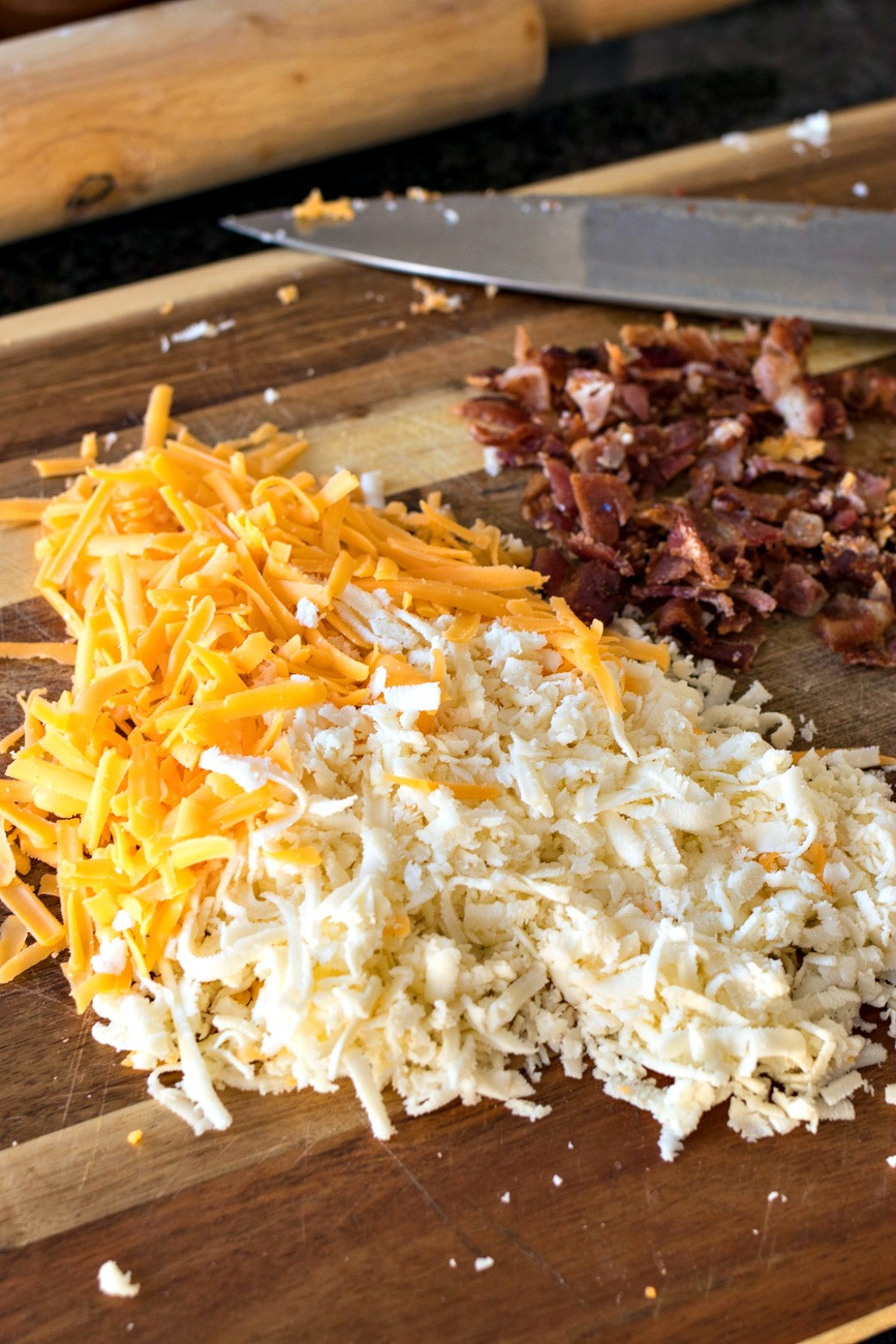 Piles of cheese and bacon on a cutting board