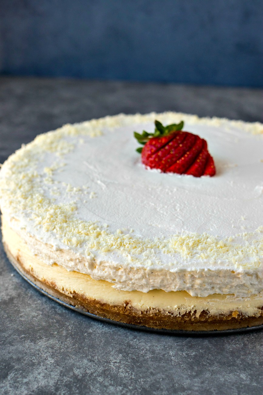 Vanilla Bean Cheesecake topped with a sliced strawberry