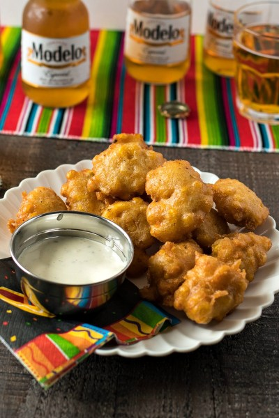 Beer Battered Corn Fritters - Corn, green chiles, and cheddar cheese are tossed in a homemade Modelo Especial beer batter and fried into delicious little fritters.