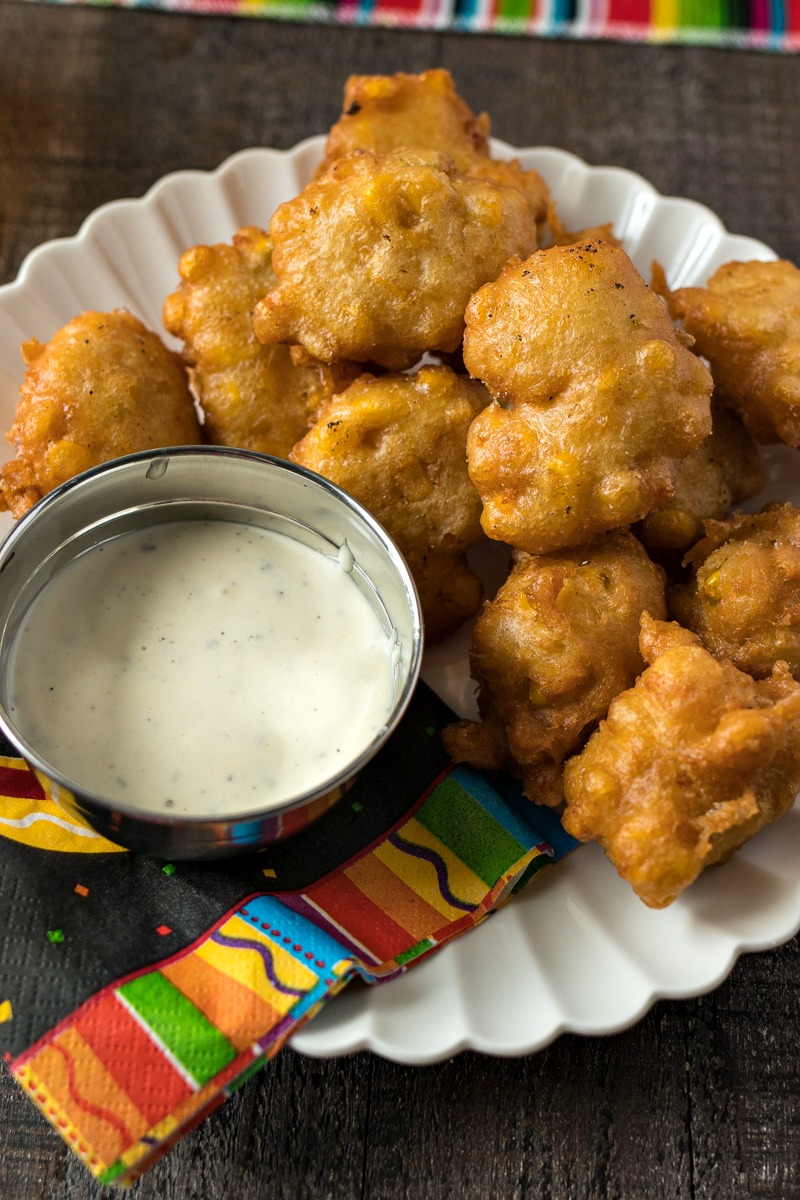 Beer Battered Corn Fritters on a plate with a dipping sauce