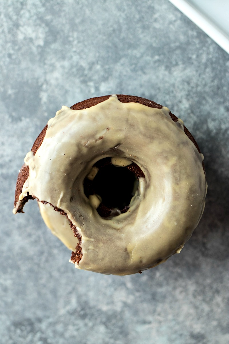 Irish Cream Chocolate Doughnuts - Dense chocolate cake doughnuts dipped in an Irish cream glaze. And what makes these even better, they're baked, not fried!