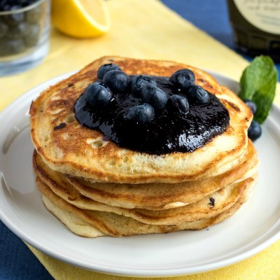 Lemon Blueberry Ricotta Pancakes - Homemade pancakes are given the gourmet treatment with the addition of fresh lemon zest, blueberries, and creamy ricotta cheese. Served with blueberry syrup for an added punch of flavor.