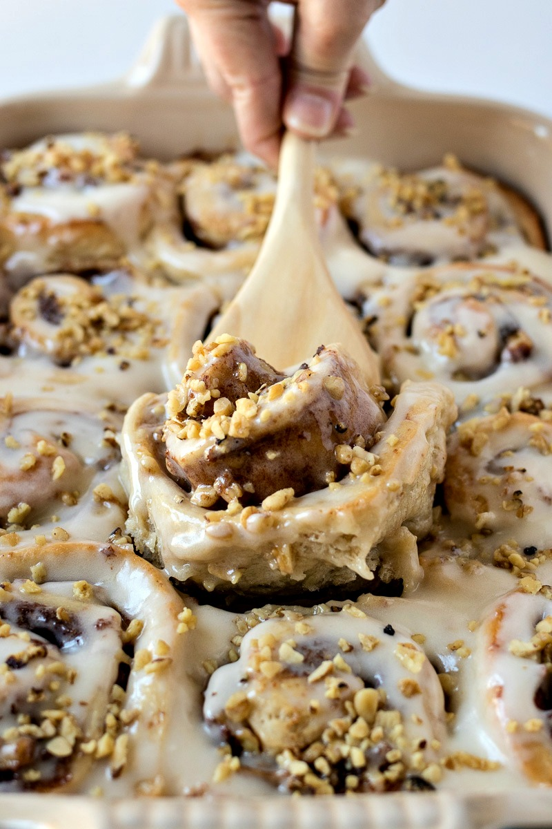 Scooping a Banana Nut Cinnamon Roll out of the pan with a wooden spatula