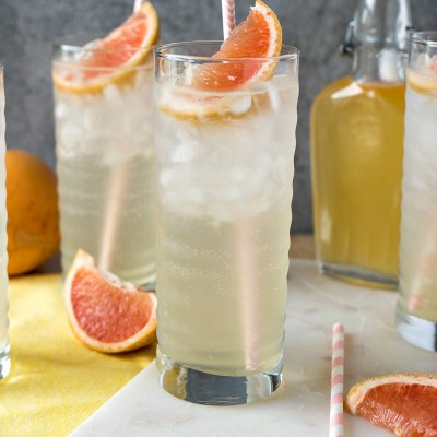Homemade Grapefruit Soda in two glasses with a glass bottle of grapefruit syrup behind it and sliced grapefruit placed around the glasses, shot from the front