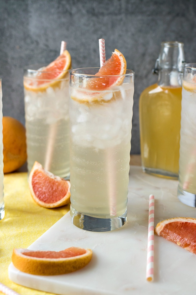 Homemade Grapefruit Soda - Homemade grapefruit syrup is added to sparkling water and finished with crushed ice and a pink straw to make the perfect refreshing drink