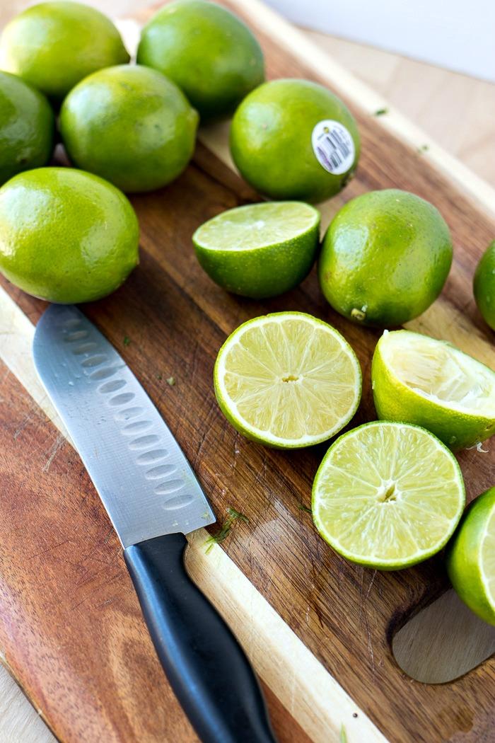 Limes cut in half on a cutting board