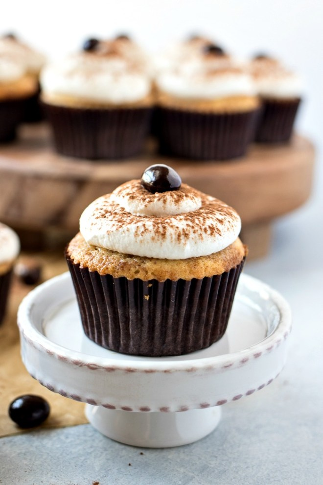 Tiramisu Cupcakes - A mini, easy-to-eat version of the classic Italian dessert. Made with vanilla cupcakes brushed with espresso and topped with a marscapone whipped cream.