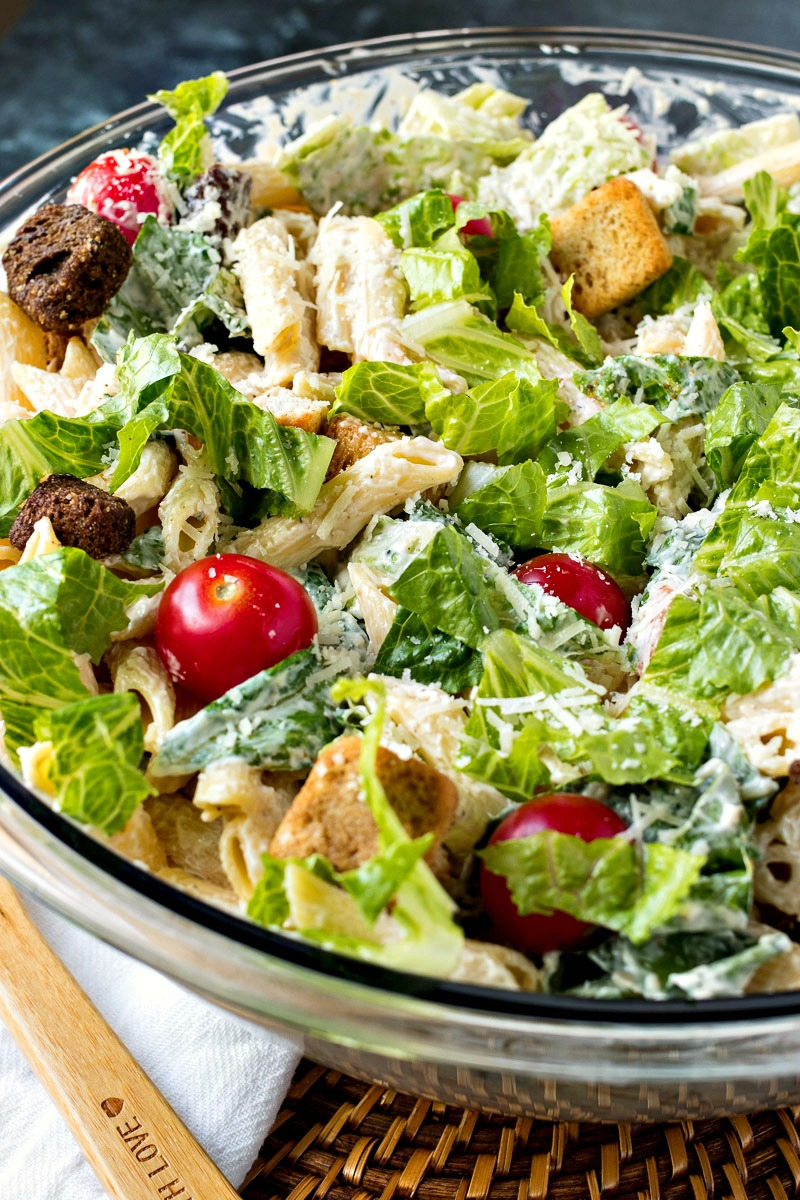 Closeup on a bowl of Caesar Pasta Salad with cherry tomatoes and croutons on top