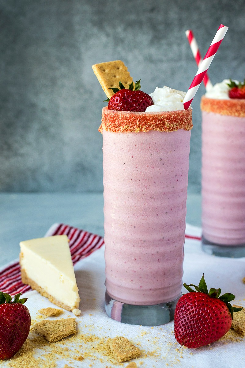 Strawberry Cheesecake Milkshake next to a piece of cheesecake and a strawberry