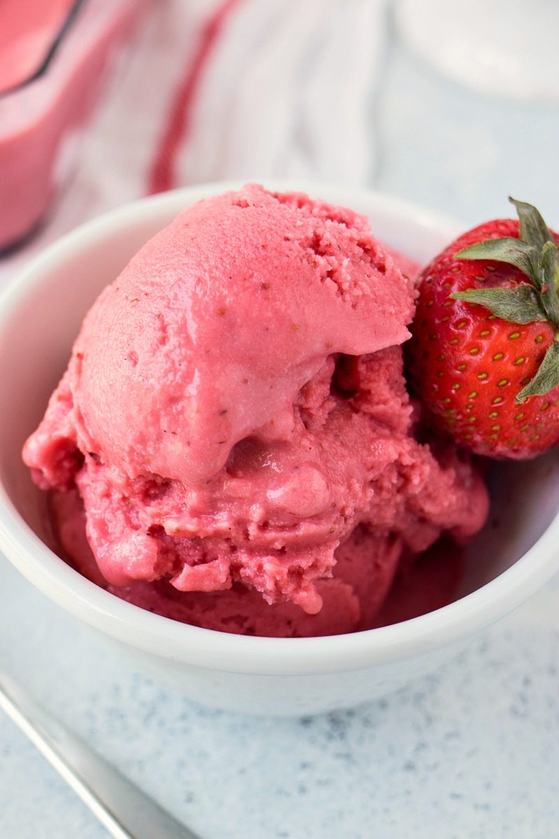 Closeup on a bowl of Strawberry Coconut Sorbet and the strawberry