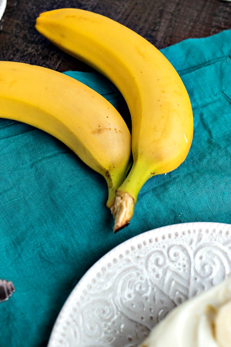 Two bananas in front of a plate