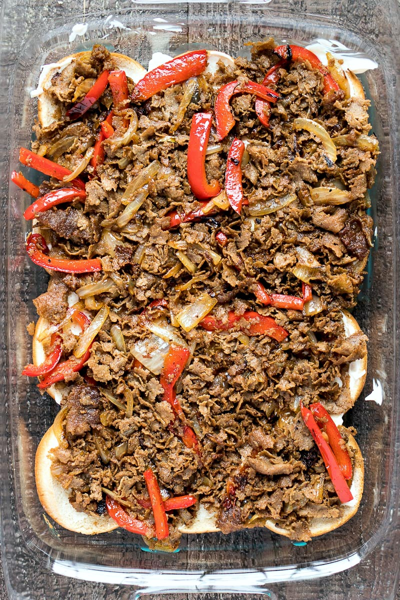 Pan of sliced steak, onions and peppers on top of the slider buns
