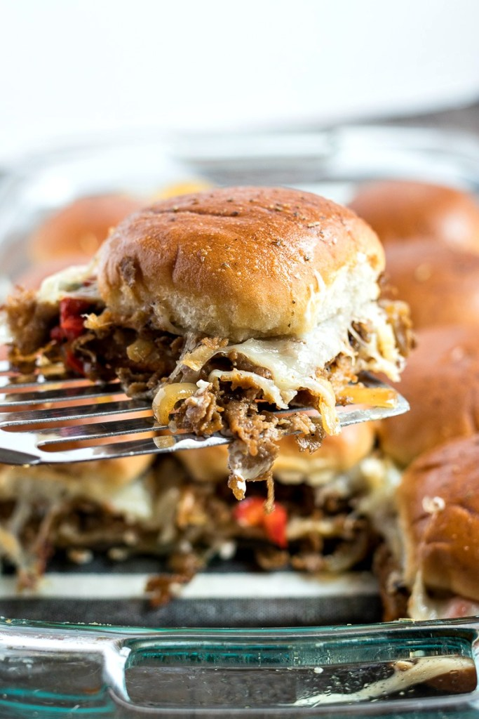 a spatula holding up a Philly Cheesesteak Slider with a glass dish with more cheesesteak sliders in it, shot from the front