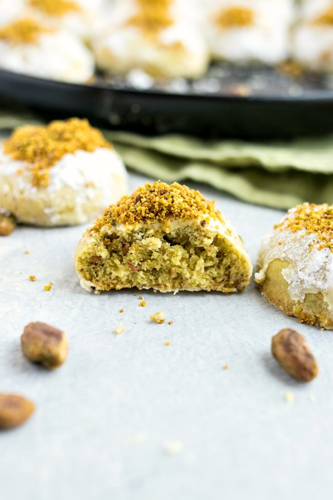 Pistachio Snowball Cookie cut in half to show the green pistachio inside