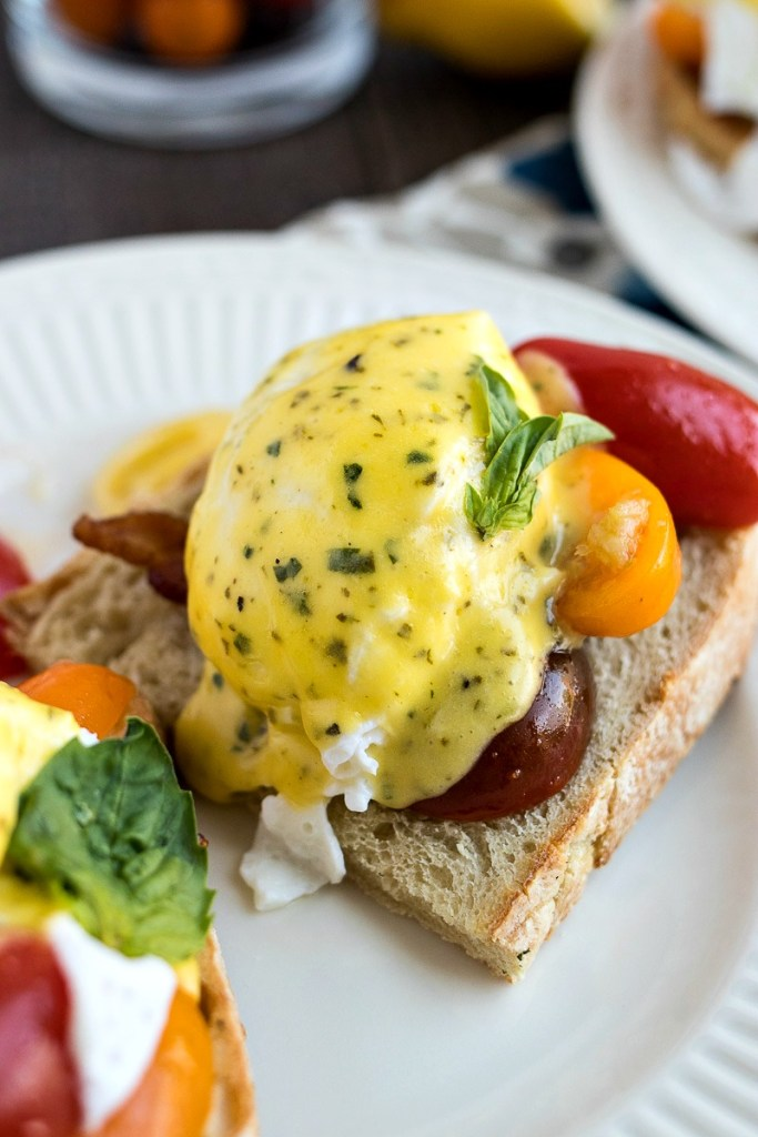 BLT benedict topped with a poached egg, peppers, hollandaise sauce and bacon