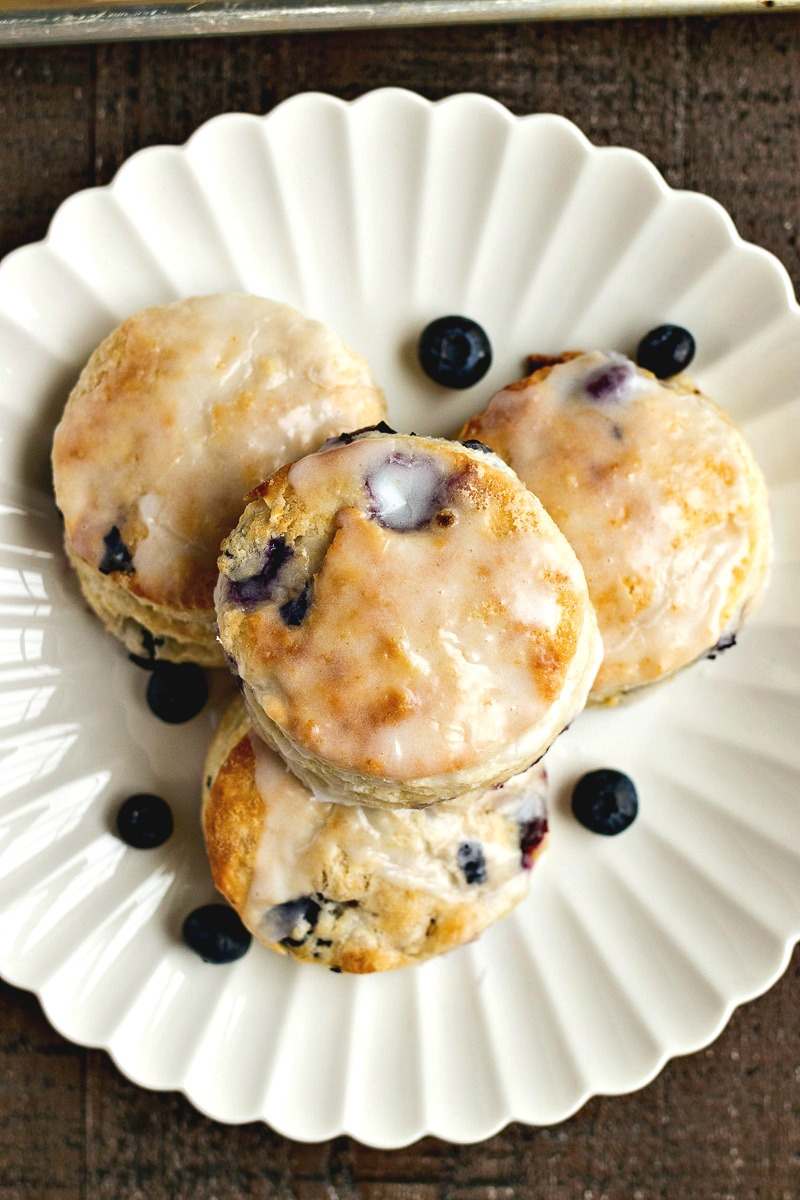 Stack of Blueberry Biscuits on a plate with whole blueberries