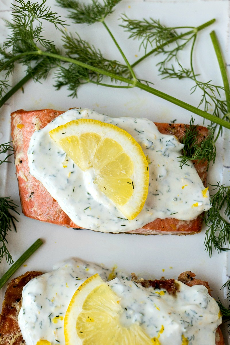 Salmon covered in creamy lemon dill sauce with a slice of lemon