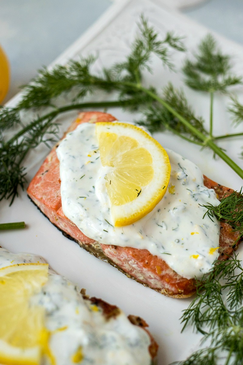 Creamy Dill Salmon topped with dill sauce and a lemon slice
