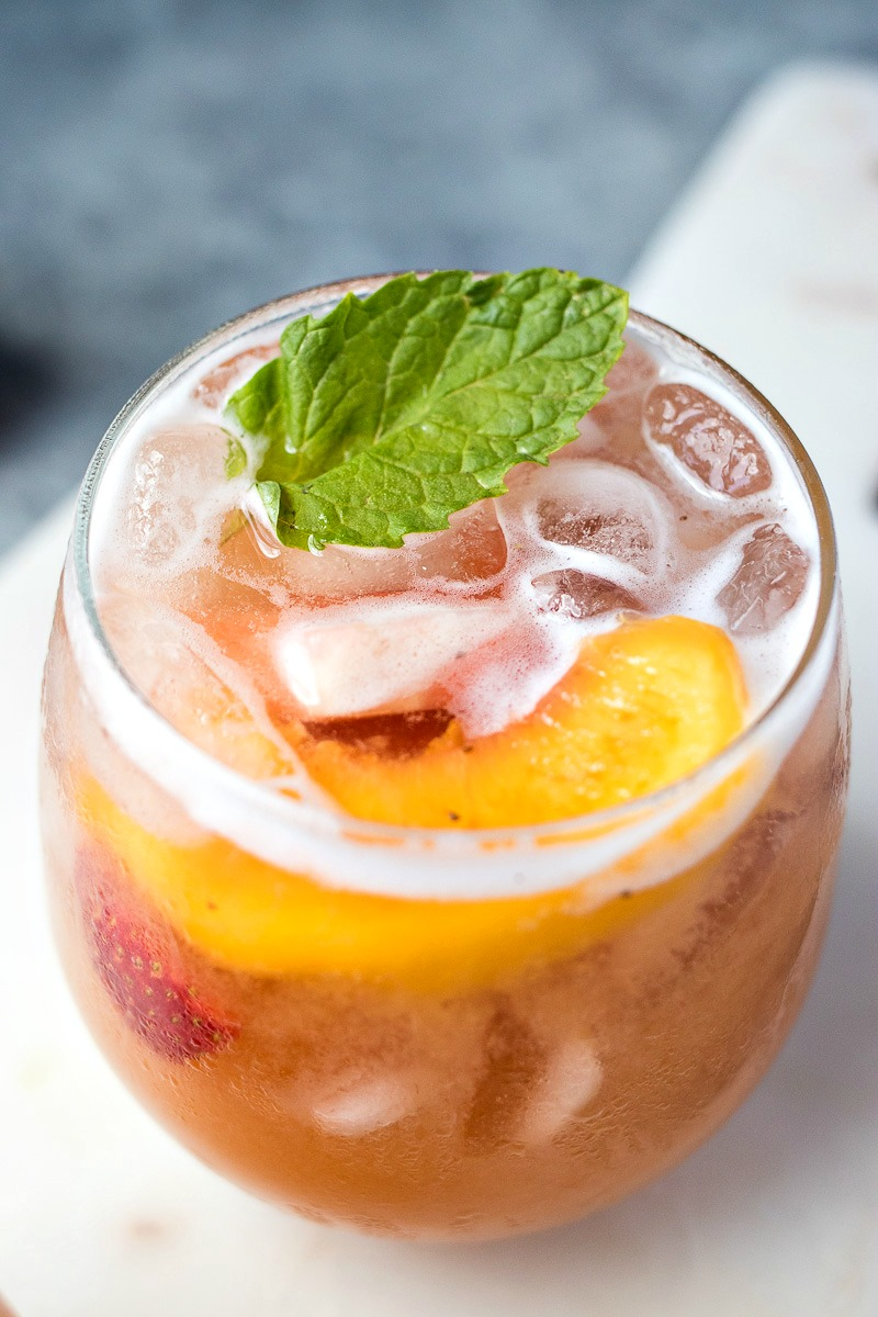 Closeup of a glass of Strawberry Peach Sangria with peach slices and pieces of strawberries