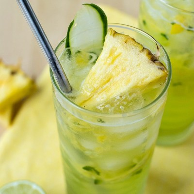 zoomed in shot of cucumber pineapple gin refreshers on a cloth napkin with a slice of cucumber and a half of a lime and pineapple slices in the background, shot from a side angle