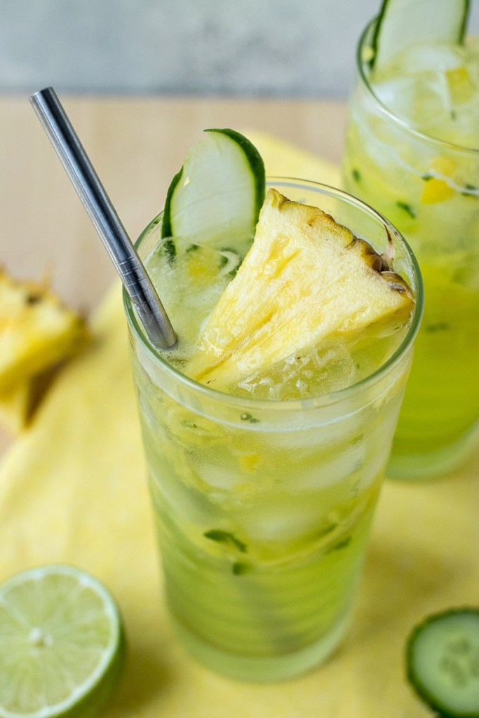 Glass of Cucumber Pineapple Gin Refresher with a pineapple chunk and a lime slice