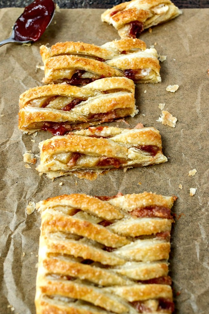 Guava Cream Cheese Pastry Braid cut into slices on parchment paper with a spoon of guava jelly on it, shot from overhead