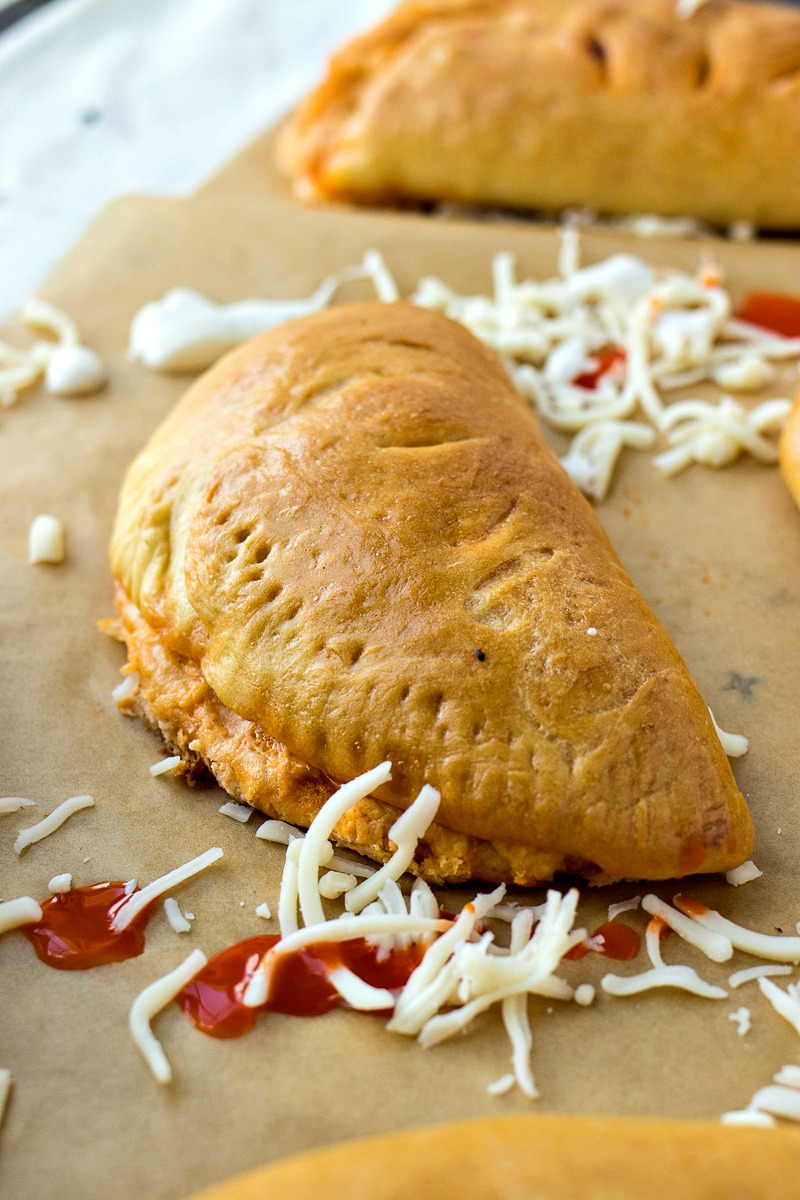 Buffalo Chicken Pockets surrounded by shredded cheese
