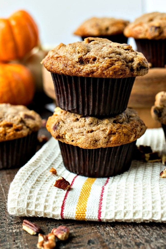 two pumpkin cinnamon crunch muffins on a towel with more muffins it the background with pecans sprinkled around and a stack of pumpkins in the background, shot from the front