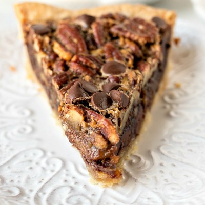 a slice of chocolate pecan pie on a plate with another plate of pie in the background, shot from a side angle
