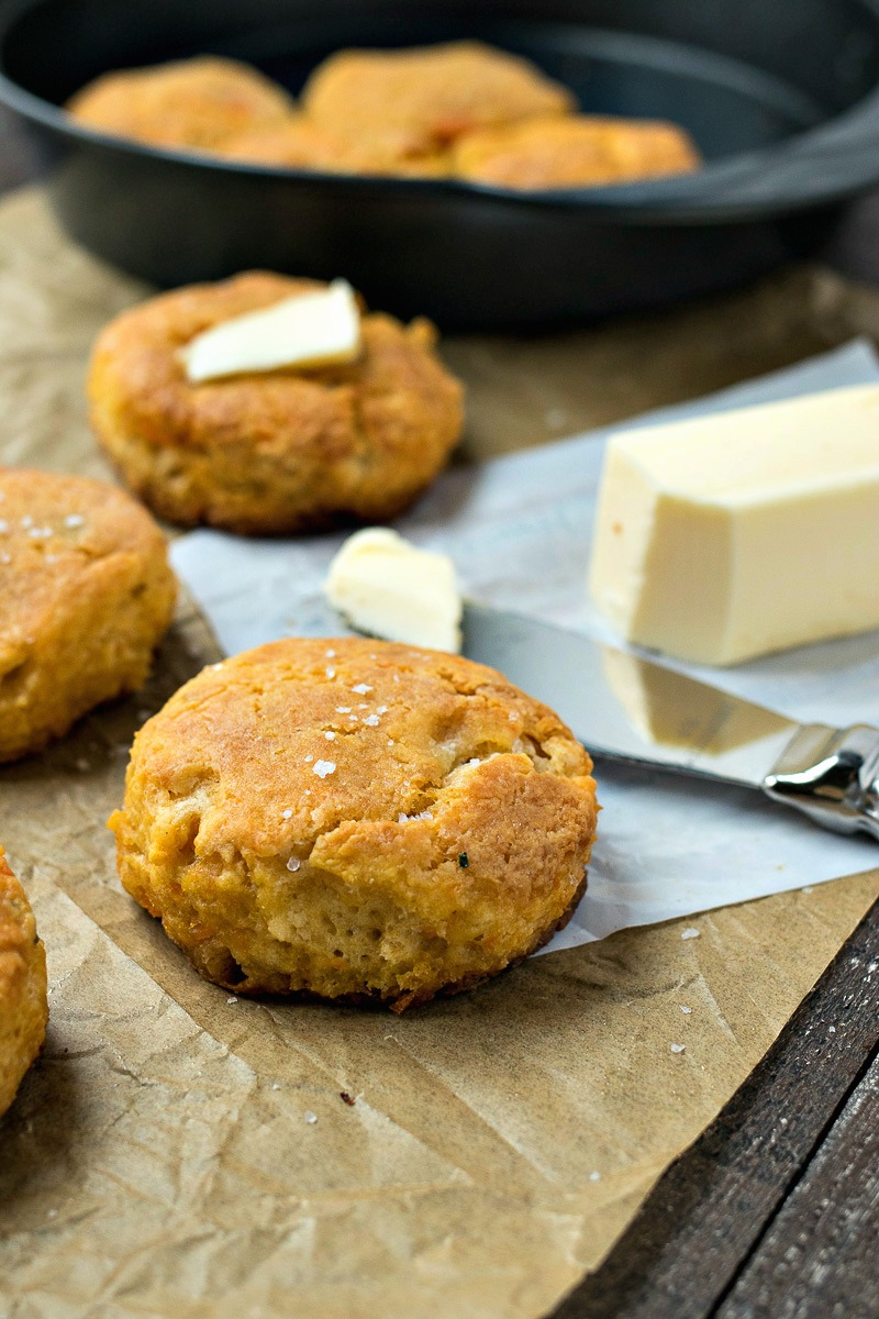 Sweet Potato Biscuits in front of the skilled of biscuits and a stick of butter
