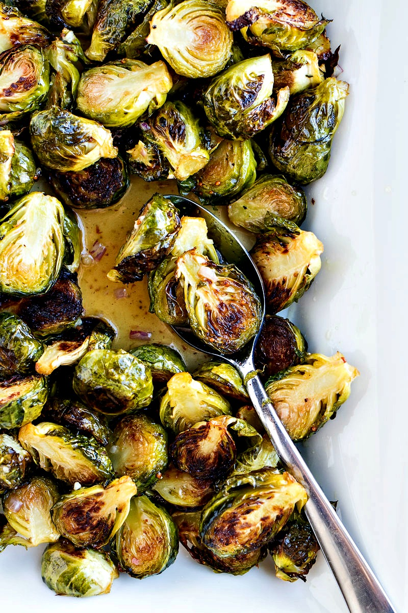 Spoonful of Roasted Brussels Sprouts with Honey Mustard Vinaigrette above the tray of them