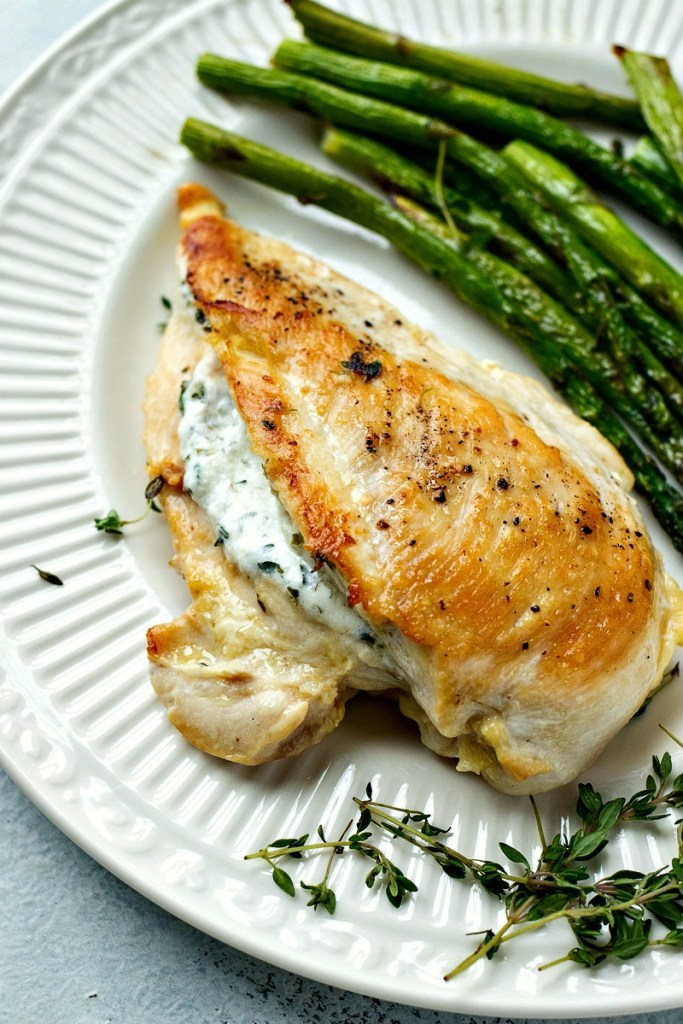 goat cheese stuffed chicken on a plate with asparagus next to it, shot from overhead