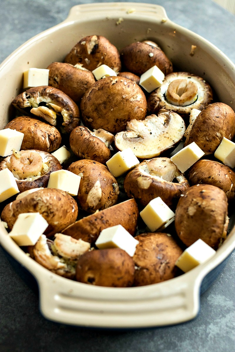 Closeup of a casserole dish of mushrooms and slices of butter
