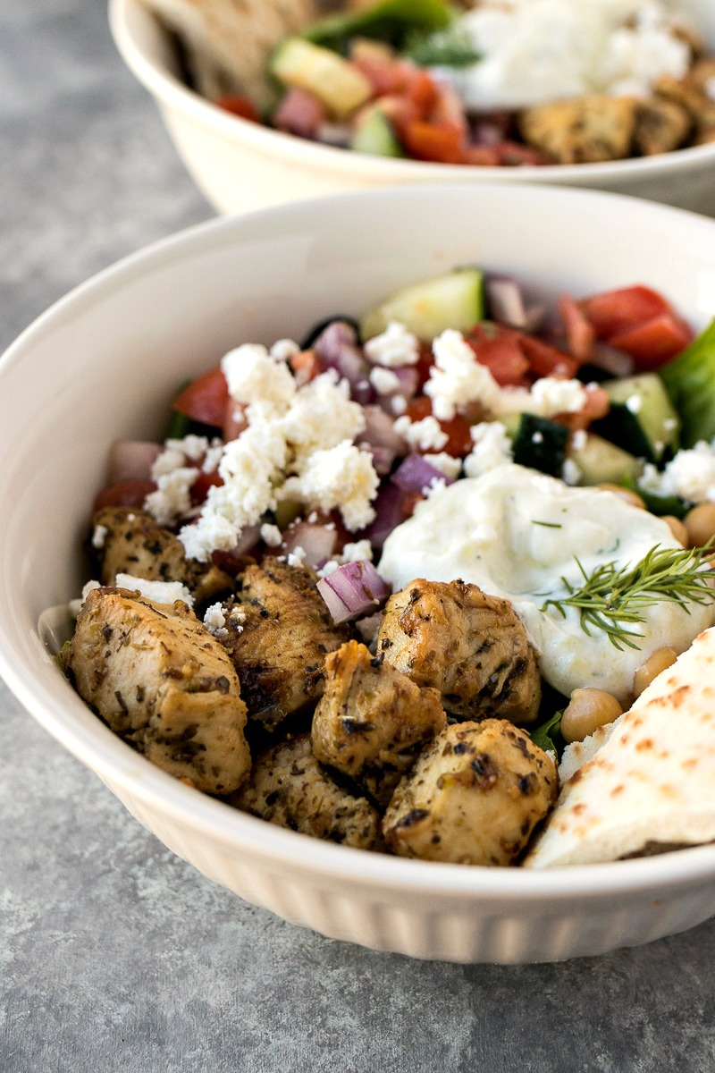Mixed greenstopped with Greek chicken, chickpeas, tomato cucumber salad, feta cheese, and homemade tzatziki sauce.