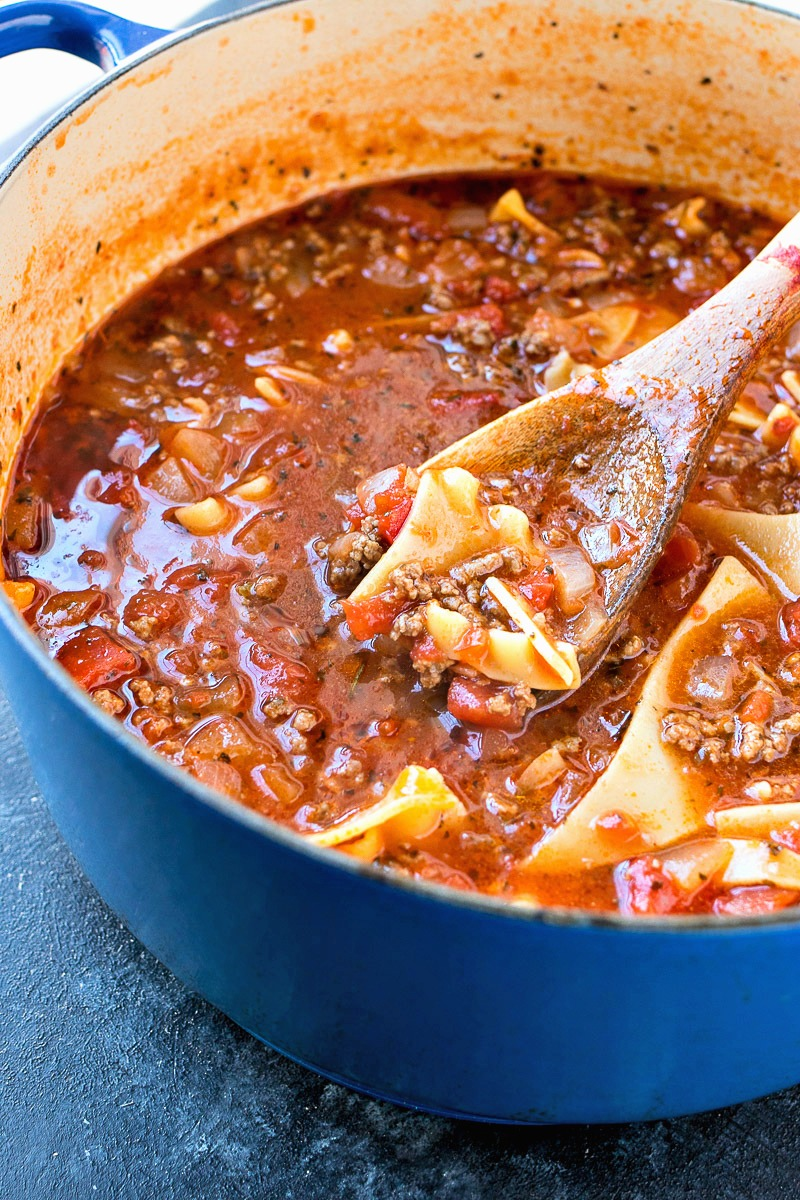 Pot of Lasagna Soup with noodles being lifted with a wooden spoon