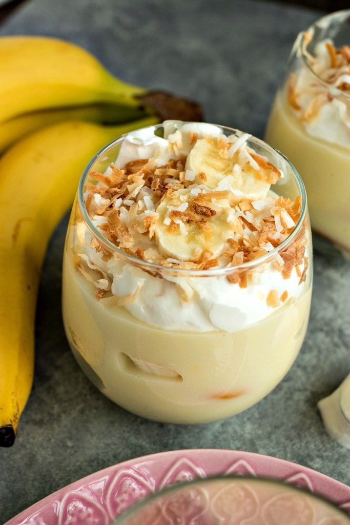 Glass of Coconut Banana Pudding in front of a bunch of bananas