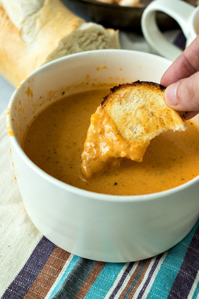 Toasted bread being dipped into lobster bisque