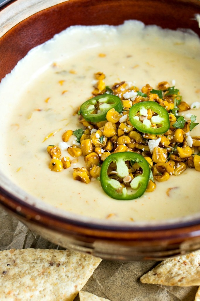 Bowl of Mexican Street Corn Queso topped with corn, cheese and jalapeno slices