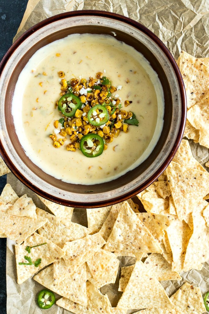Creamy white queso is cooked with green chiles and roasted corn