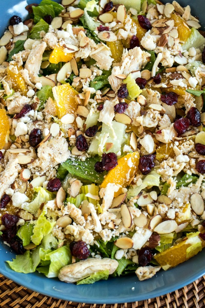 Closeup on a bowl of Citrus Almond Salad showing the almond slices, fruit, feta cheese and lettuce