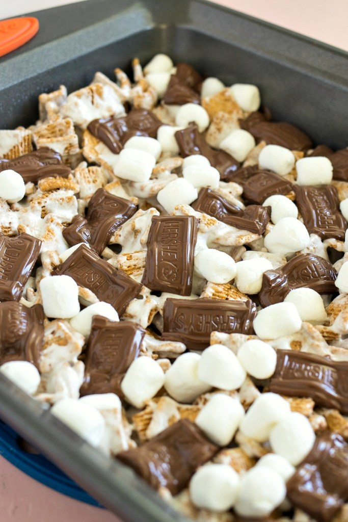 Pan of Crispy S'mores Bars topped with melted hersheys chocolate pieces and marshmallows