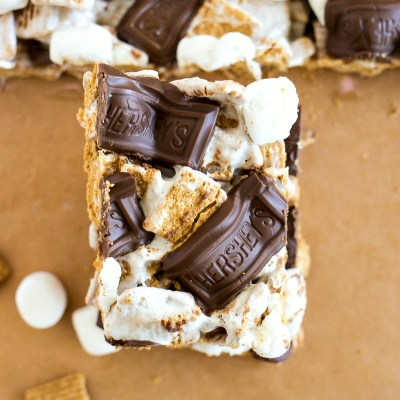 slices of crispy smores bars on parchment paper with a marshmallow and golden graham next to it, shot from overhead