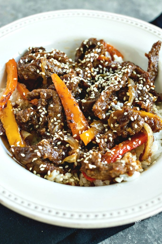 Bowl of Mongolian Beef with peppers and onions topped with sesame seeds