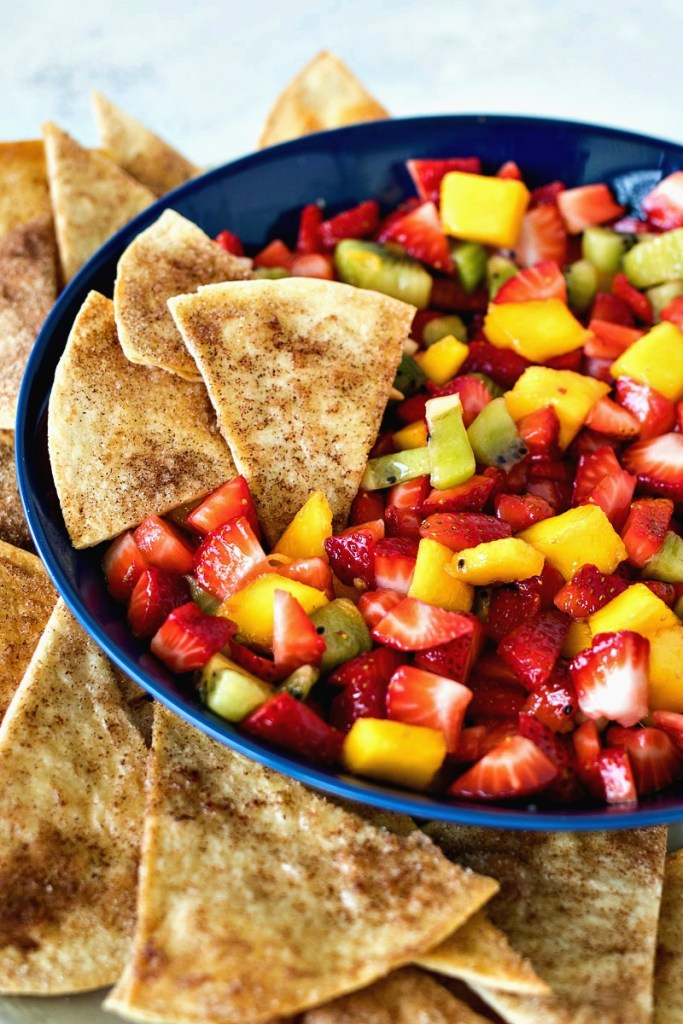 Three cinnamon chips dipped into the fruit salsa