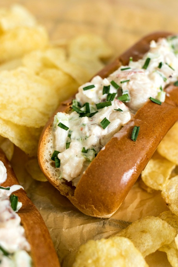 Closeup of a buttered lobster roll next to potato chips