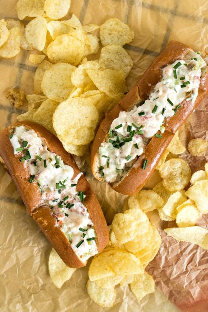 Two lobster rolls surrounded by potato chips