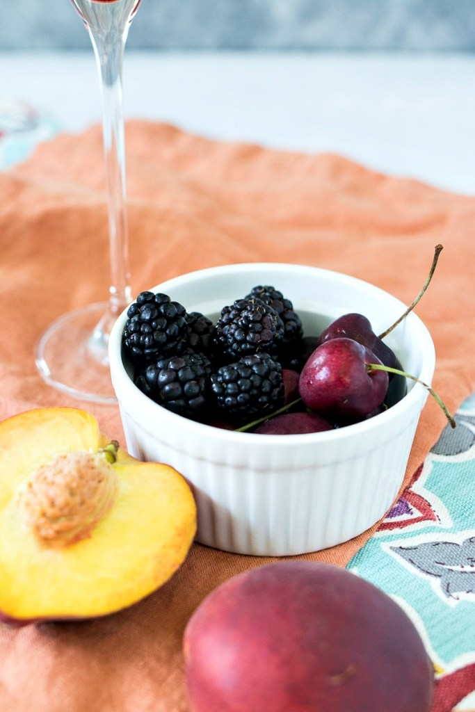 Small dish of blackberries and cherries next to half a peach